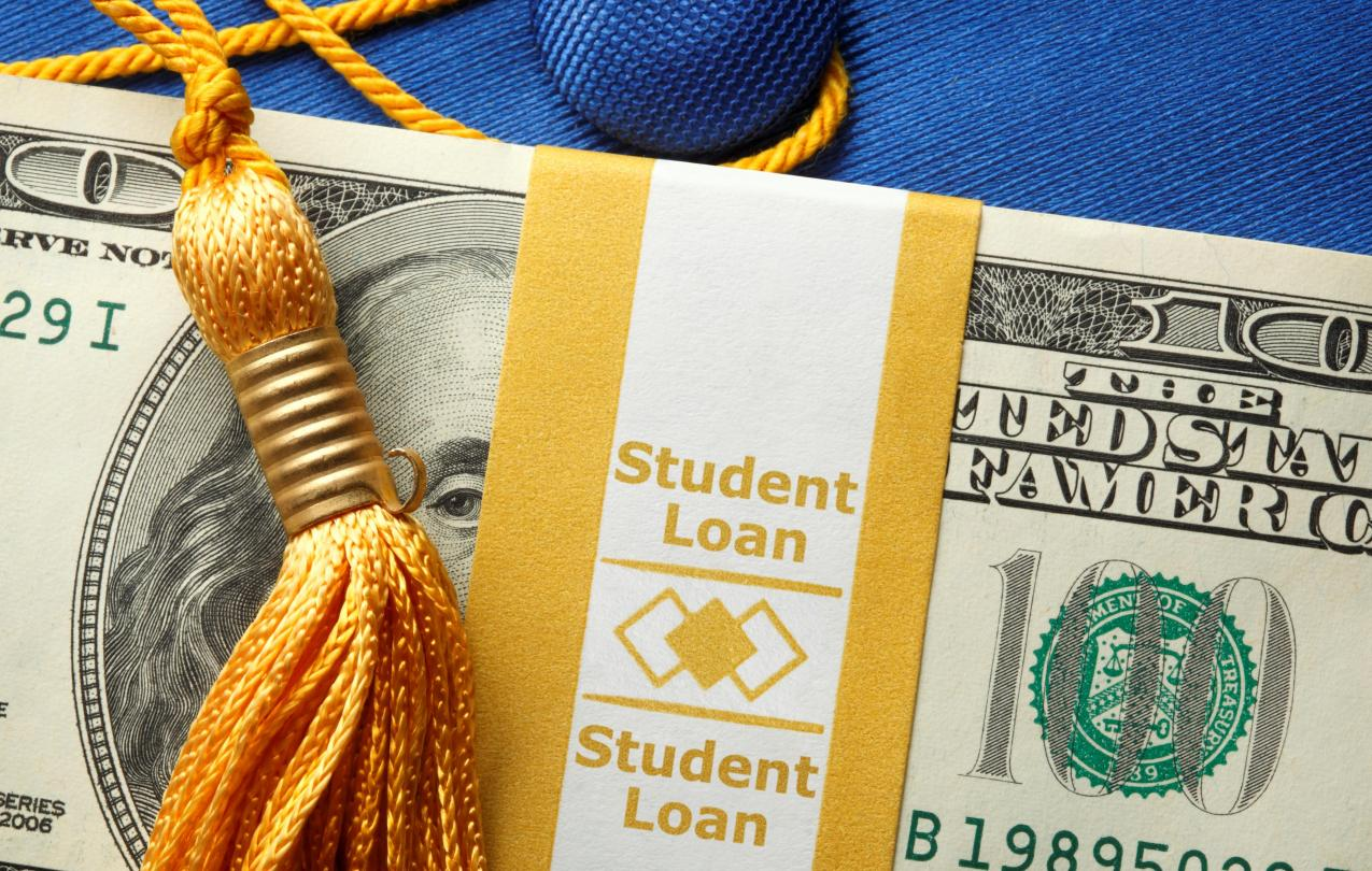 Hundred dollar bill with student loan wrapper and graduation tassel